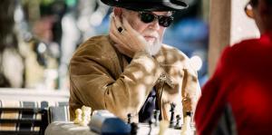 Gentleman playing chess outside